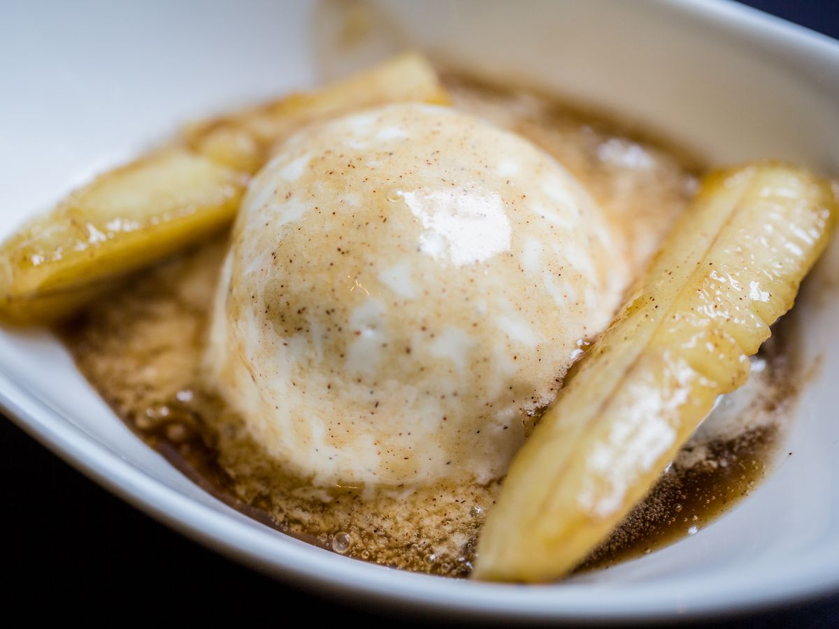 A bowl of bananas sliced lengthwise and flambéed in dark rum, banana liqueur, sugar, and cinnamon, served hot over vanilla ice cream