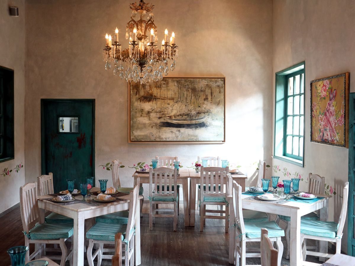 A dining room with white tables and chairs with aqua cushions and accents.