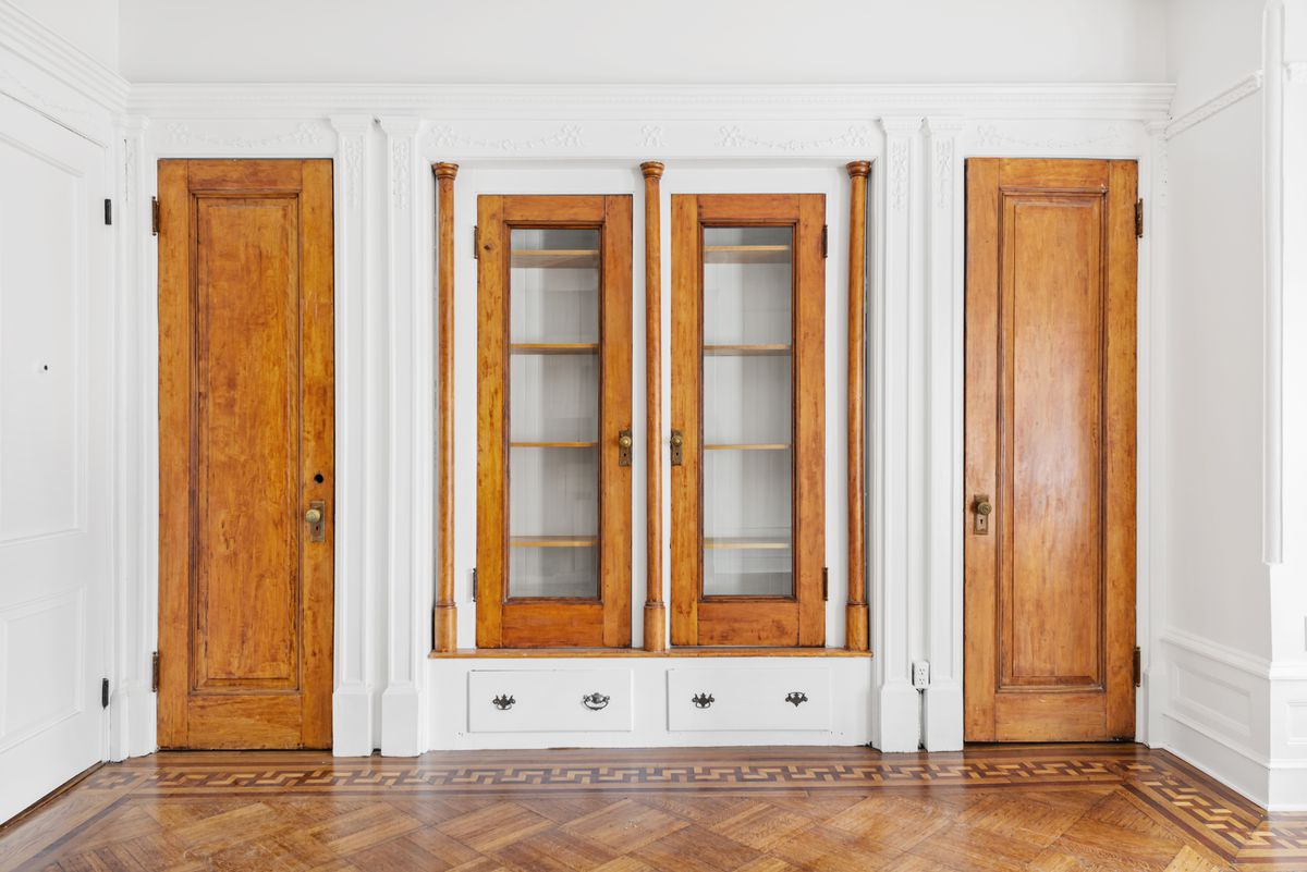 A built-in shelf with two wooden doors on either side.