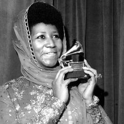 """In 1975, Franklin poses with her Grammy Award for """"Ain't Nothing Like the Real Thing."""" 