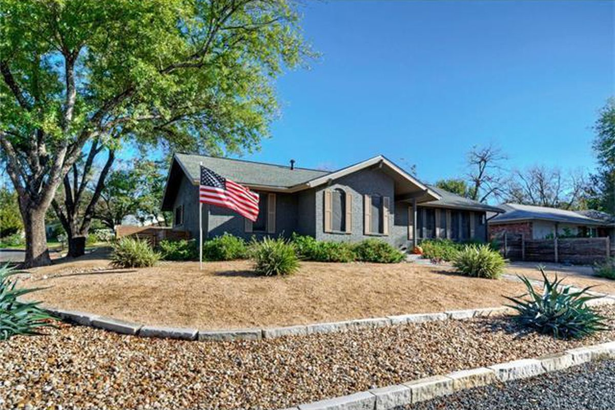 Ranch-style house with painted gray brick, American flag in front