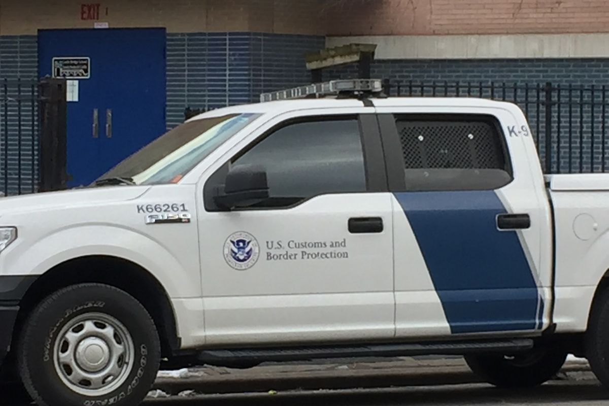 Two Customs and Border Patrol trucks parked outside of a school building in Washington Heights.
