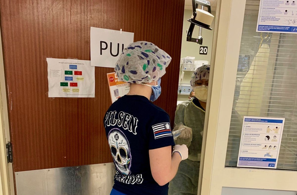As simple a task as staying or leaving a patient's room is made more complicated at Mount Sinai Hospital's emergency department by the need to wear protective gear to prevent the spread of COVID-19. Here medical supplies are passed through an open door.