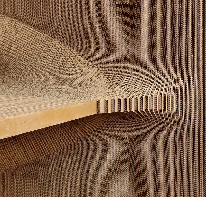 A wall made out of cardboard. The cardboard is cut into shapes which give it an undulating wave like structural shape.