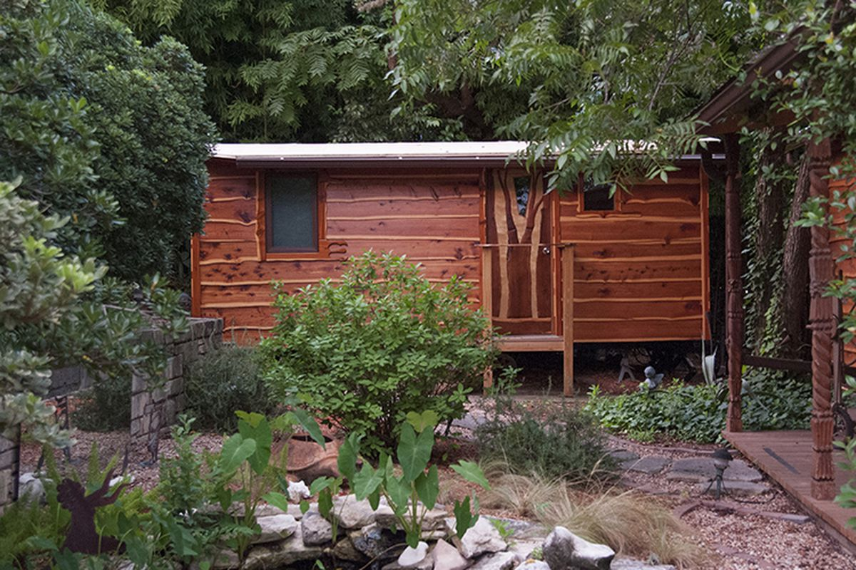 small wooden home elevated (probably on wheels) off ground, lots of trees and greenery