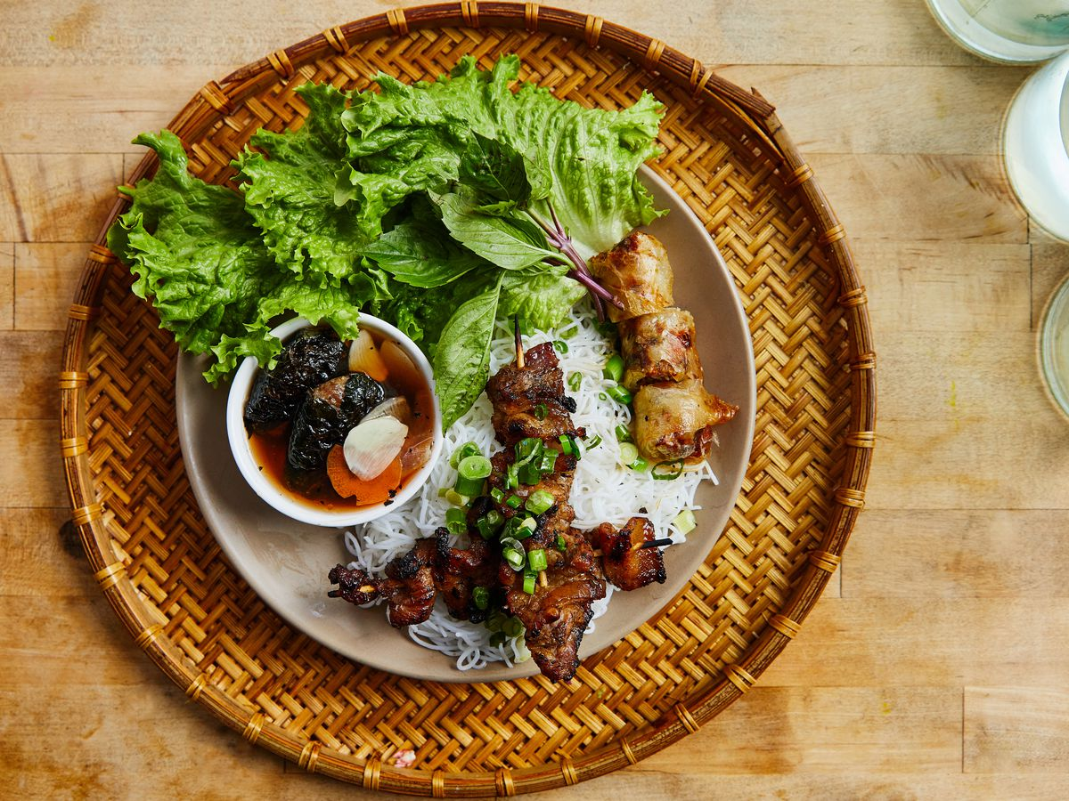 A plate with leafy green lettuce, white rice noodles, a small bowl with dipping sauce, and barbecued pork, sits on a wooden table