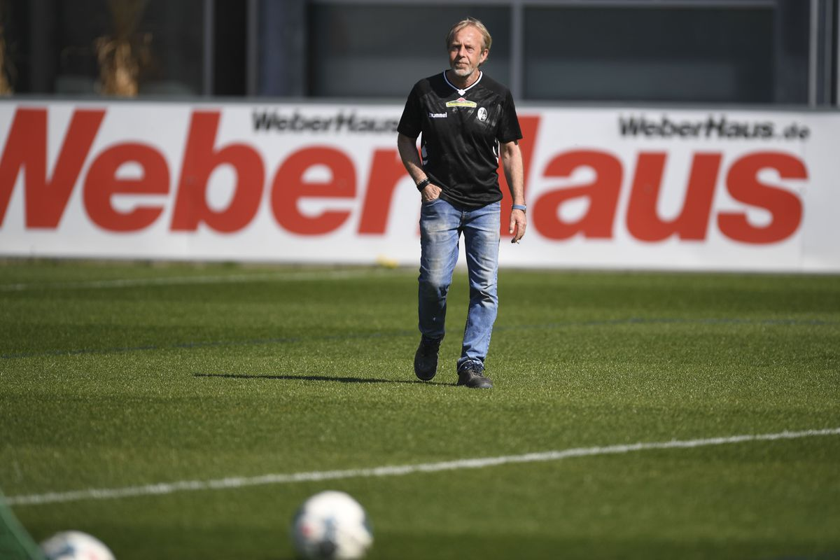 Alfred Melcher, greenkeeper of SC Freiburg, runs across the grass of the training ground.