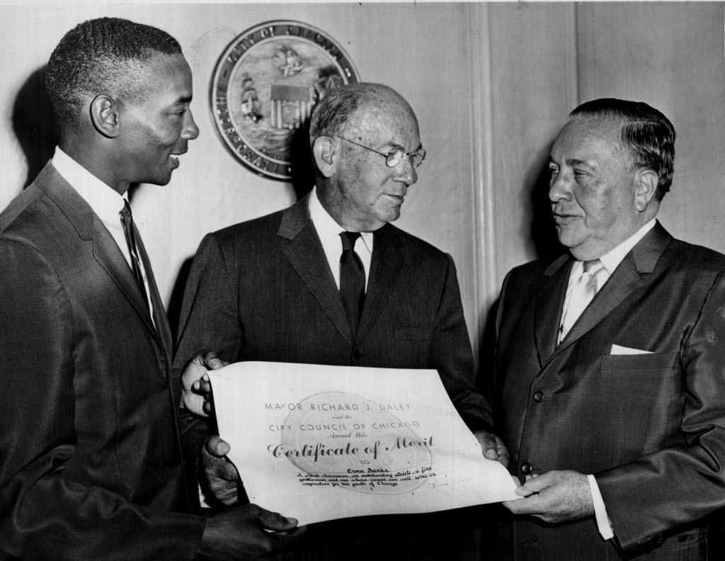 Ernie Banks(left) and Phillip R. Clarke (center) admire the document issued by Mayor Daley officially proclaiming Saturday as Ernie Banks Day, 1964.   Sun-Times library
