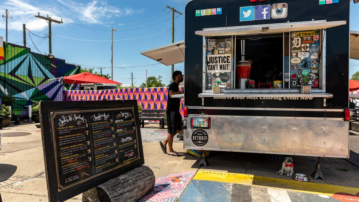 A customer orders food outside of the Detroit 75 Kitchen food truck on a sunny day during summer 2020.