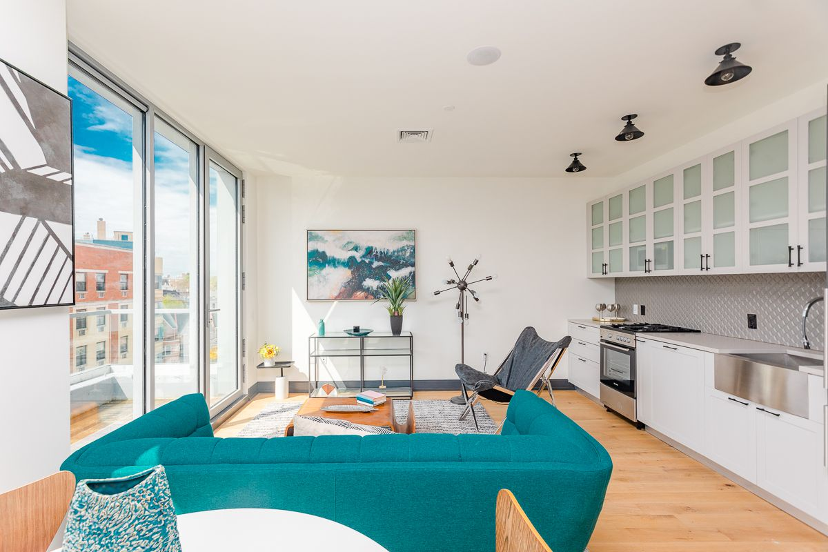 A living area with hardwood floors, white walls, an open kitchen, a bright blue couch, and large glass sliding doors that lead to a balcony.