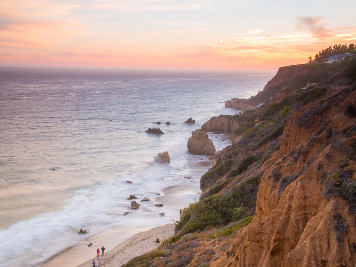 A cliff face next to a sandy beach and ocean. There is a sunset in the sky.