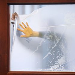 A worker installs concealment film on interior windows as Dragonfly Wellness in Salt Lake City prepares to open as the first of Utah's 14 medical cannabis pharmacies on Monday, March 2, 2020.
