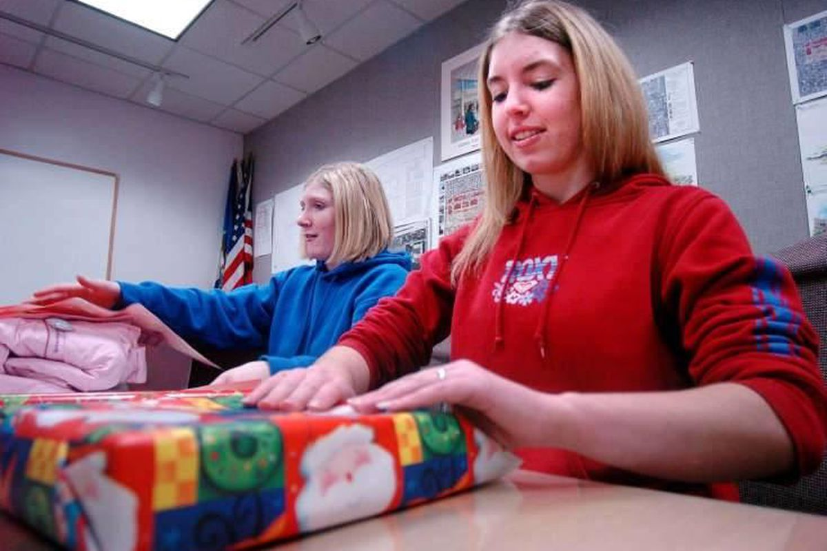 Liz Clegg (left) and Charlyn Sellers(right) wrap Christmas Presents from the Giving Tree at Valley Fair mall Monday December 20, 2004. A social-media campaign suggests shoppers give to people in need on Tuesday after Thanksgiving.