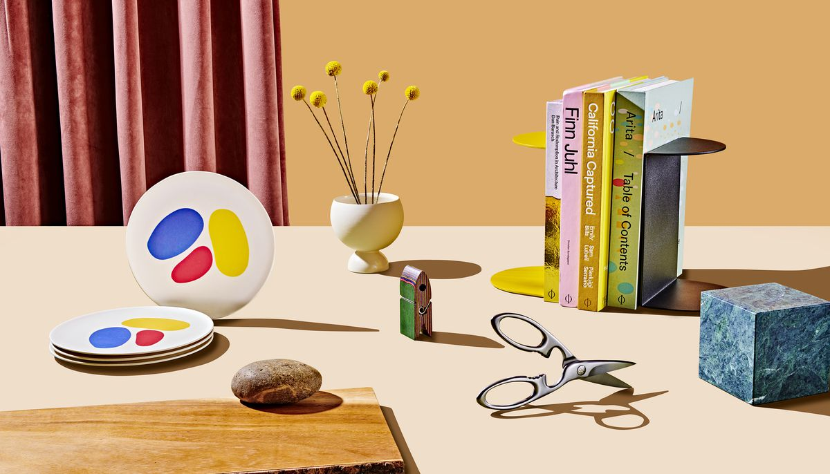 A group of products which are all featured in the 2019 Curbed Holiday Gift Guide. There are plates with a colorful design, kitchen shears, a bag clip, a white flower vase, and a set of yellow and black bookends. The products are sitting on a flat surface.