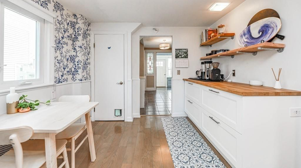 The edge of the kitchen, with another counter across from a table and two chairs, and leading to another room.
