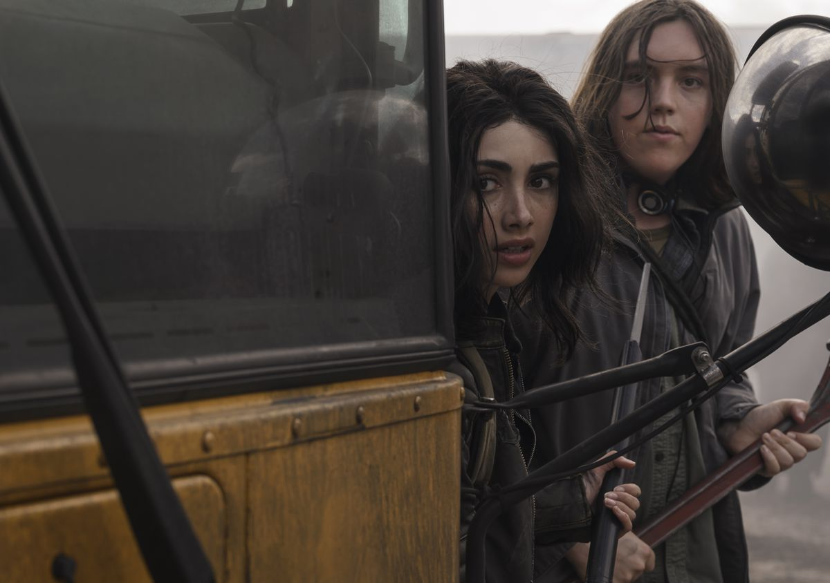 two young girls hide behind a school bus while hunting zombies in The Walking Dead: World Beyond