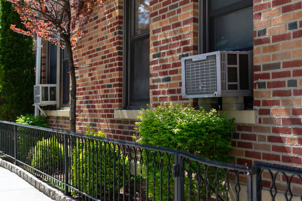 A window AC unit on the exterior of a brick apartment window with a low iron fence and green shrubs nearby.