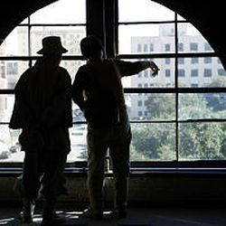 Tourists point out window at Sixth Floor Museum where fatal shot was likely fired.