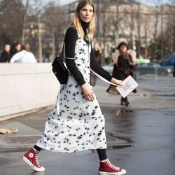 Veronkia Heilbrunner adds a casual touch to an Ellery dress with red Converse sneakers.