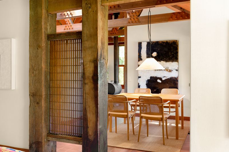 An iron grating sits between two large beams of wood as a screen between the dining room and the living room.