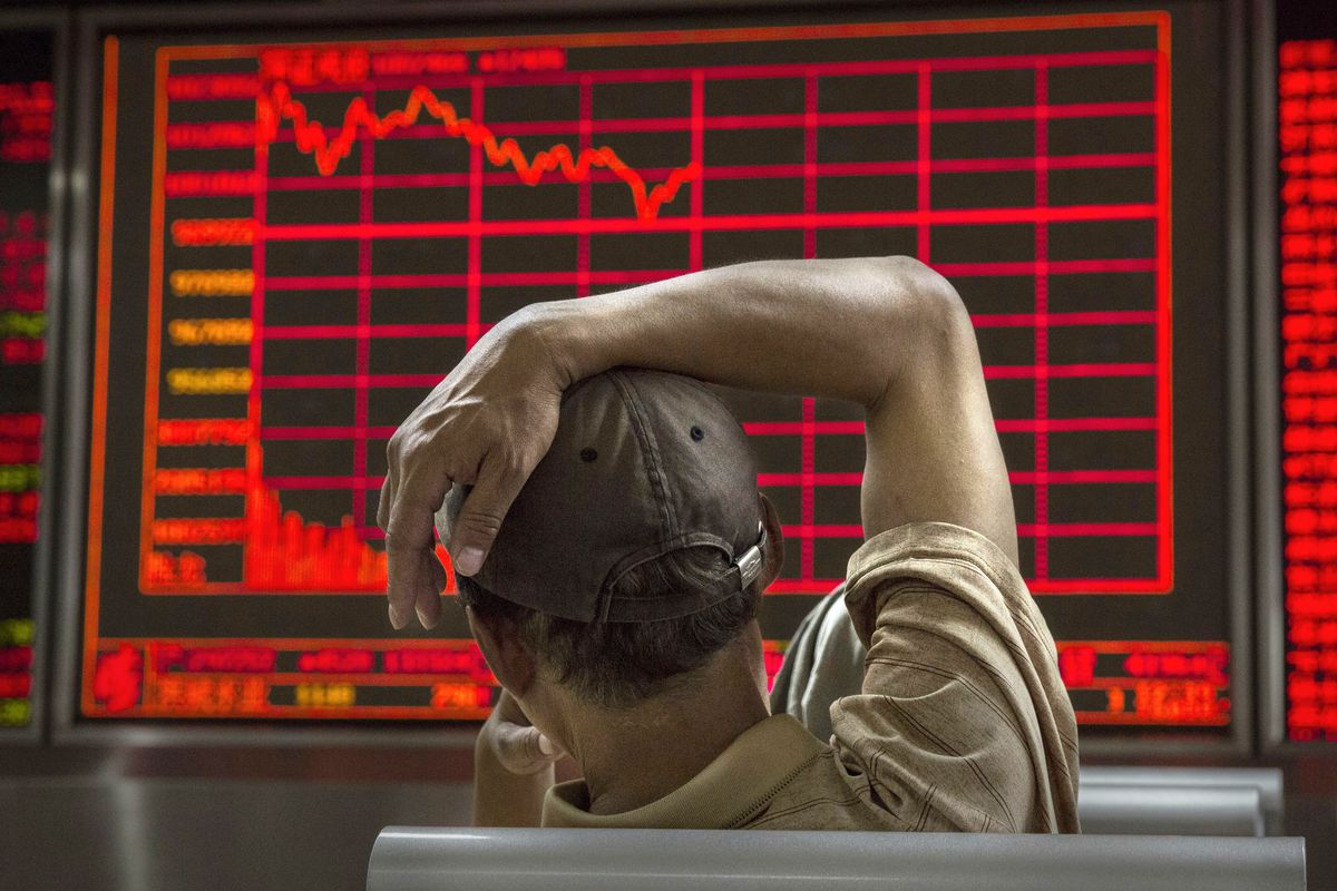 A Chinese day trader watches a stock ticker at a local brokerage house on August 27, 2015, in Beijing, China.