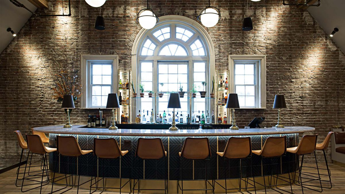 This interior shot shows the second floor bar at the Longfellow Bar in Cambridge. The triangular wall is brick-lined, and the bar is round. Dark beige high-top chairs sit in front of it.