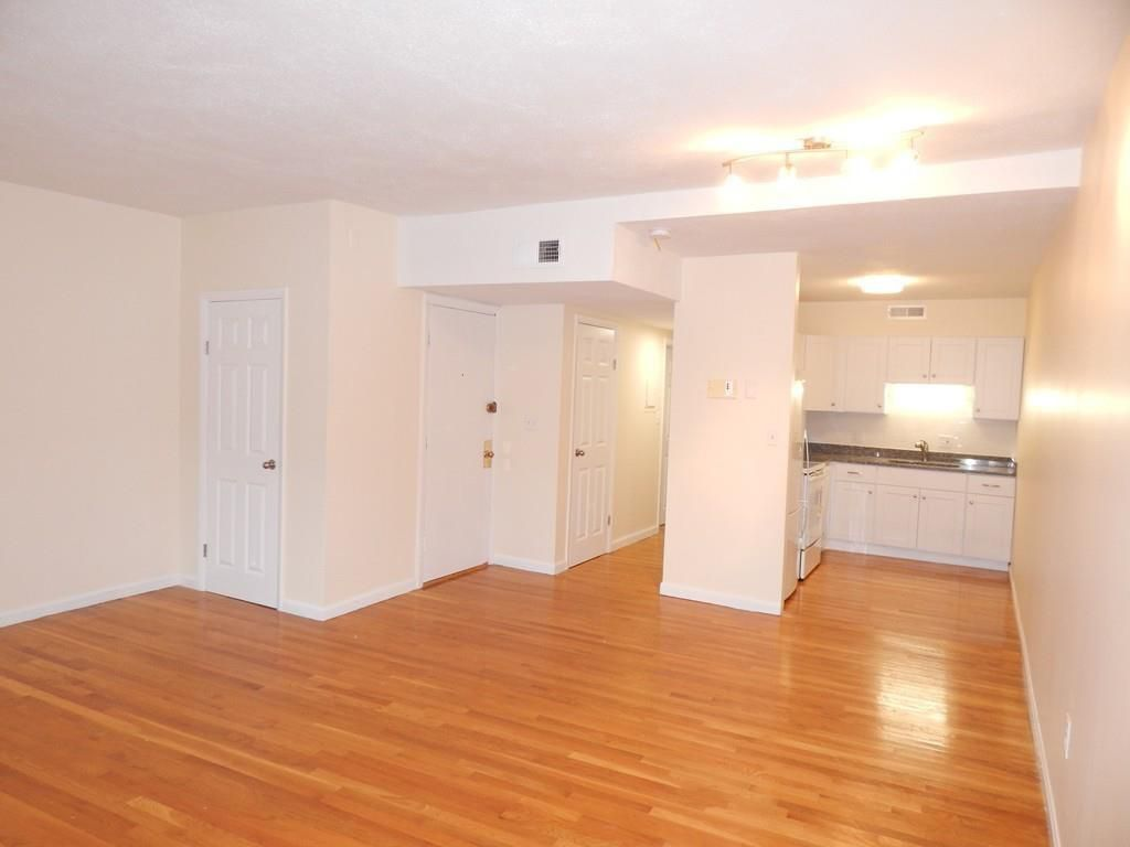 An empty living room-dining room area with a kitchen at the back.