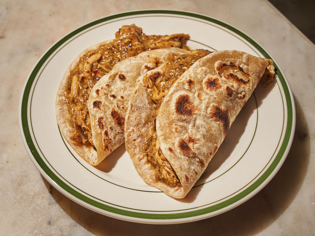 Two lightly charred flour tortillas are stuffed with pollo guisado on a plate