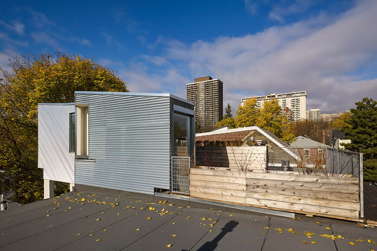 Rooftop view of a small boxy volume clad in corrugated aluminum and a garden as well as the skyline beyond.