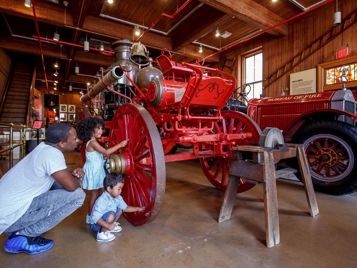 Children and an adult touch a wheel on an old firefighting vehicle on display at the Fireman's Hall Museum in Philadelphia.