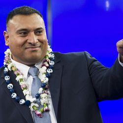 BYU's new head football coach Kalani Sitake points to a friend in the audience as he sits down for a press conference in Provo Monday, Dec. 21, 2015.