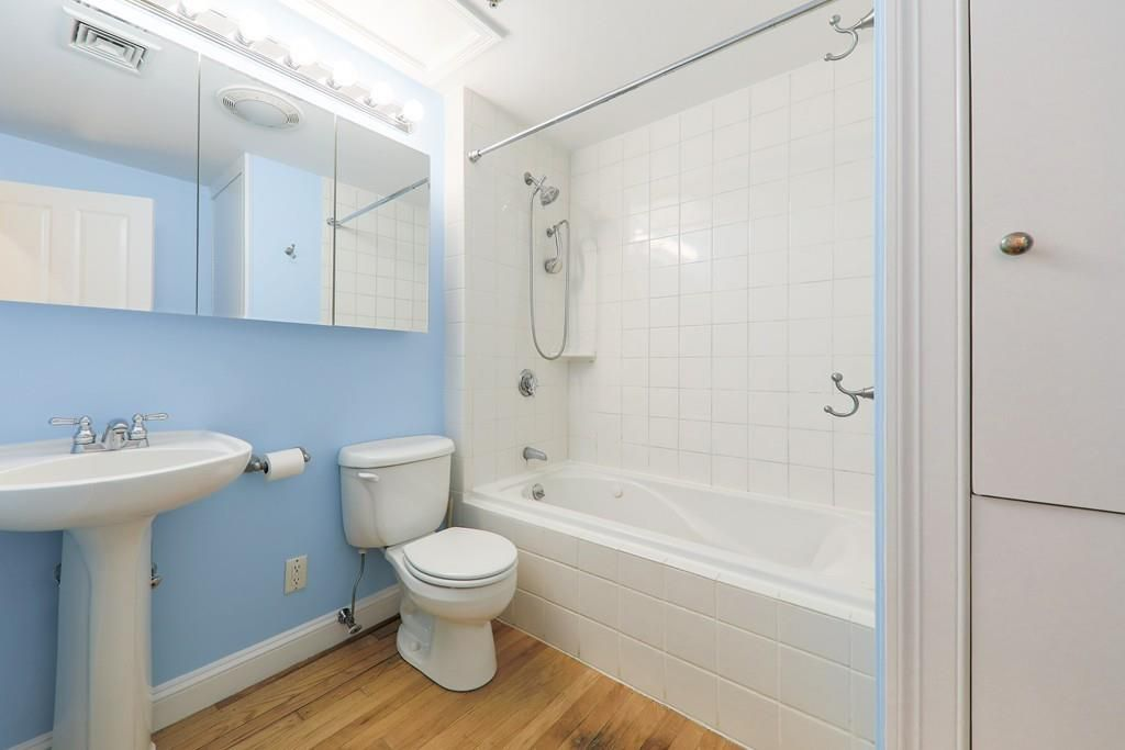 A bathroom with a sink next to a toilet next to a shower with no curtain.