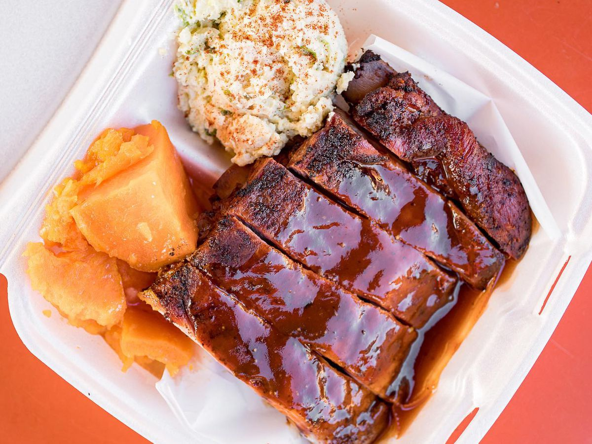 Styro form container filled with bbq ribs and coleslaw.