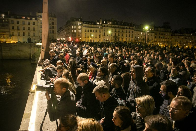Parisians and tourists gather on the Pont de la Tournelle to watch the cathedral as it burns.