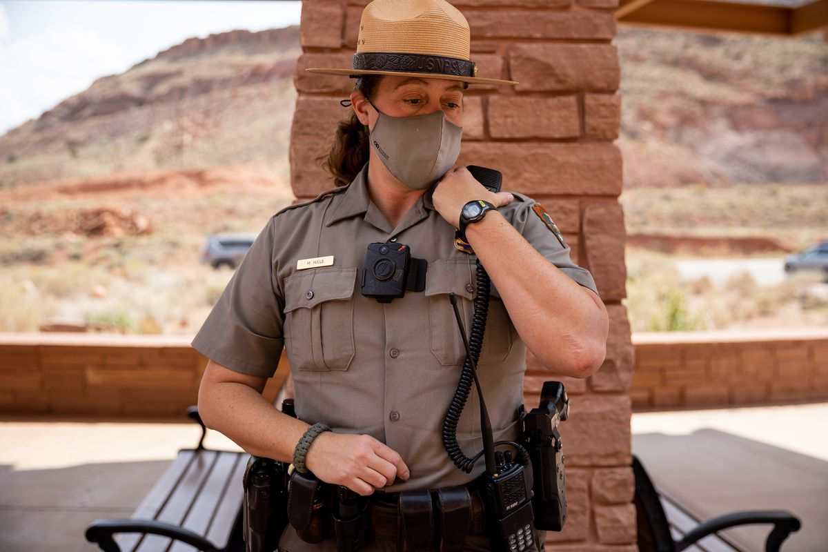 National Park Service ranger Melissa Hulls, the visitor and resource protection supervisor for Arches National Park, listens to a call on her radio outside of the park's visitors center on Sunday, Sept. 19, 2021.