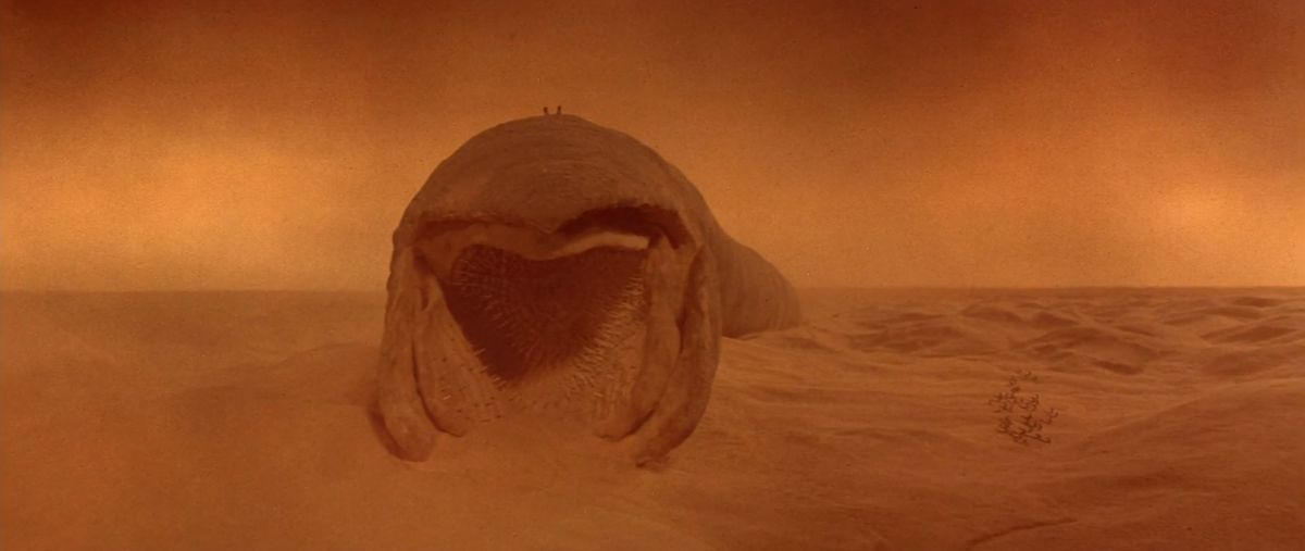 Two spots on top of a massive sand worm. Dozens of smaller dots — fremen fighters — stream in from the right side of the frame.