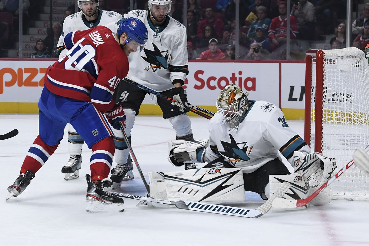 Aaron Dell #30 of the San Jose Sharks makes a save in front of Joel Armia #40 of the Montreal Canadiens in the NHL game at the Bell Centre on October 24, 2019 in Montreal, Quebec, Canada.