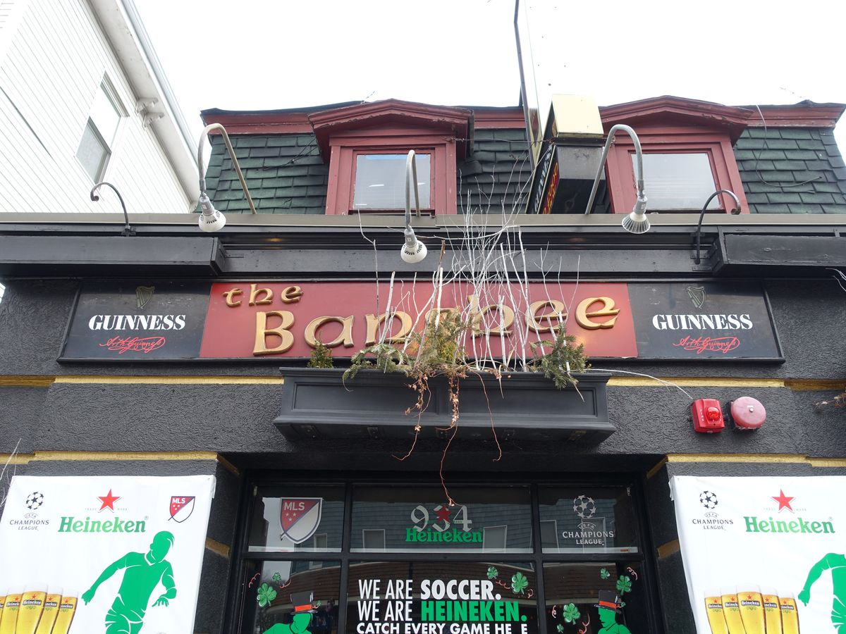Black exterior of a bar with red signage that says the Banshee in gold font.