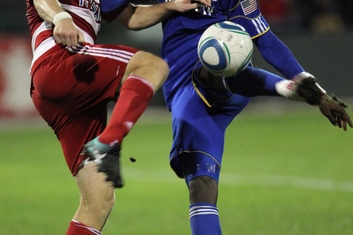 KANSAS CITY MO - SEPTEMBER 25:  Kei Kamara #23 of the Kansas City Wizards shoots as Kyle Davies #15 of FC Dallas defends during the game on September 25 2010 at Community America Ballpark in Kansas City Missouri.  (Photo by Jamie Squire/Getty Images)