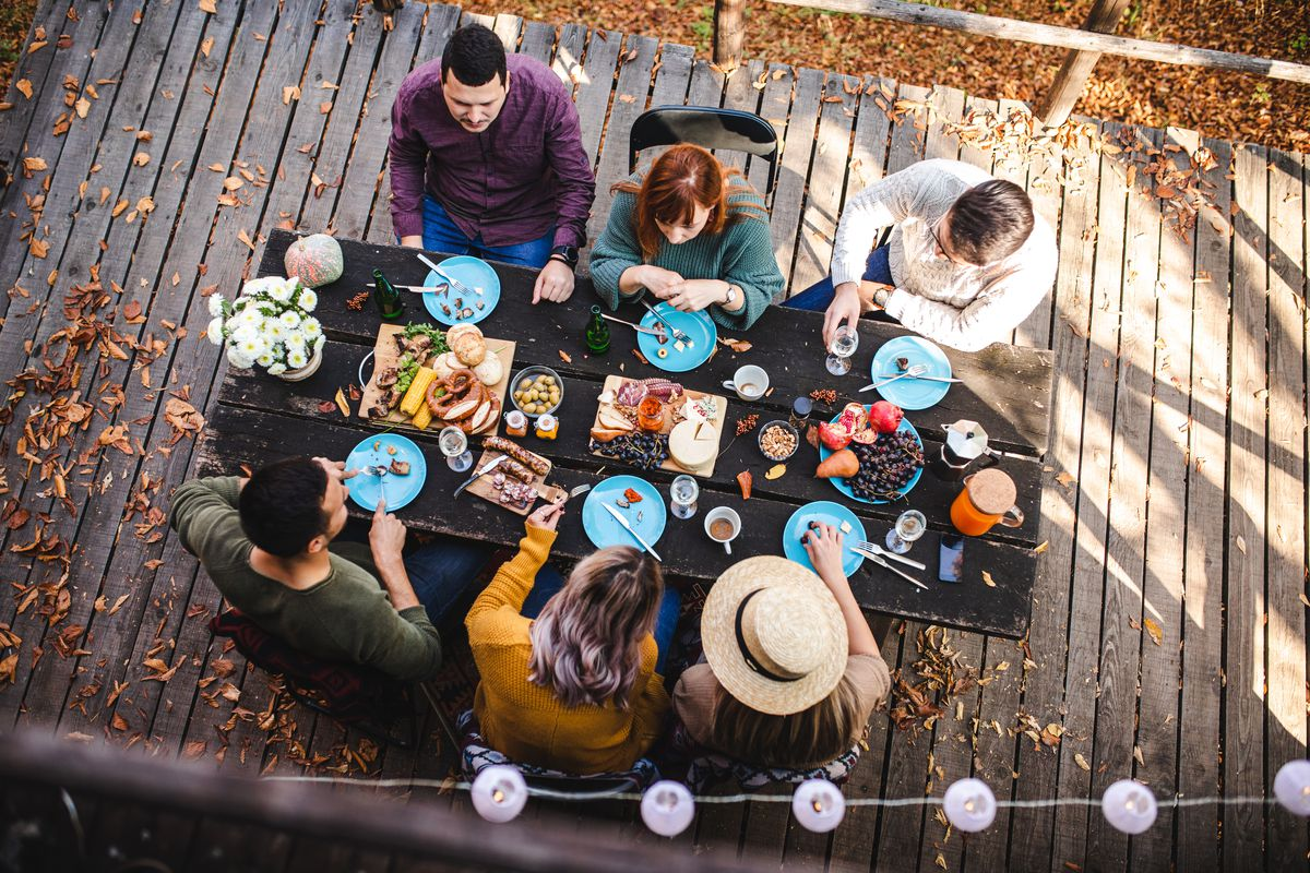 A group of people congregate outdoors for a meal.