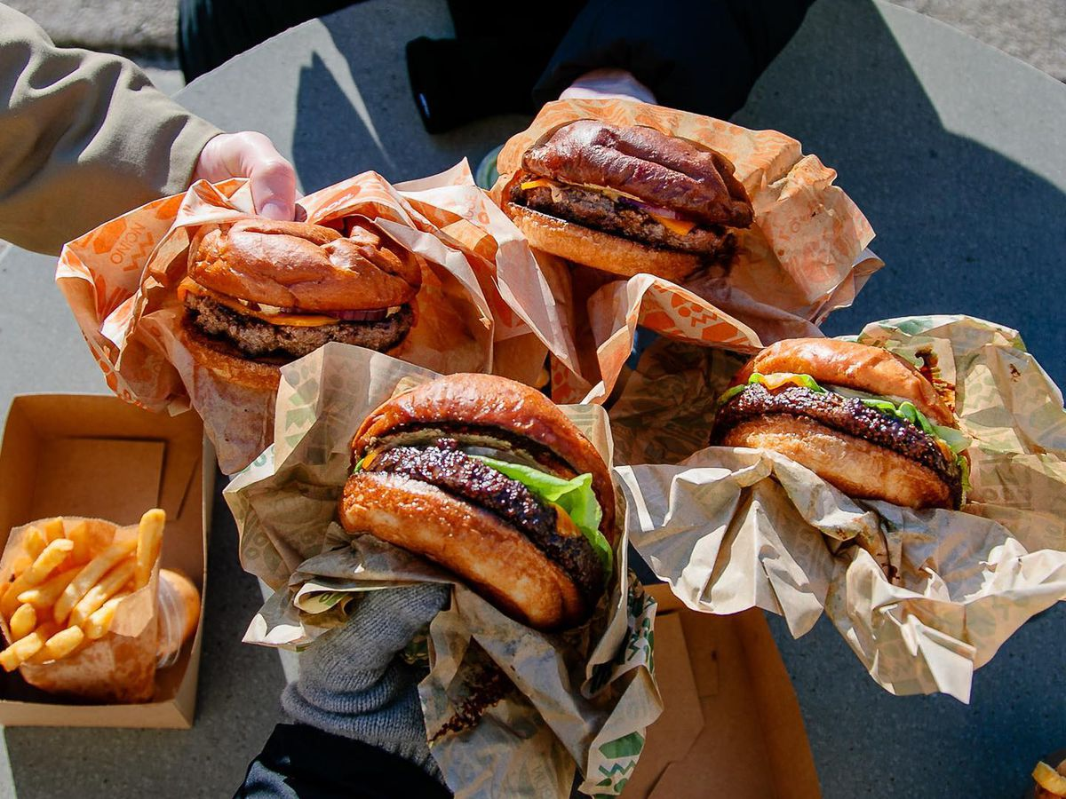Several people holding burgers together over a metal outdoor table