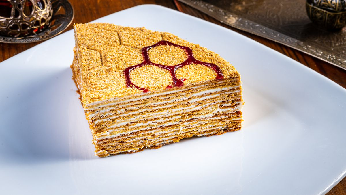 A slice of Sharbat's honey cake shows of airy layers mixed with a light milk cream whipped on the stove.