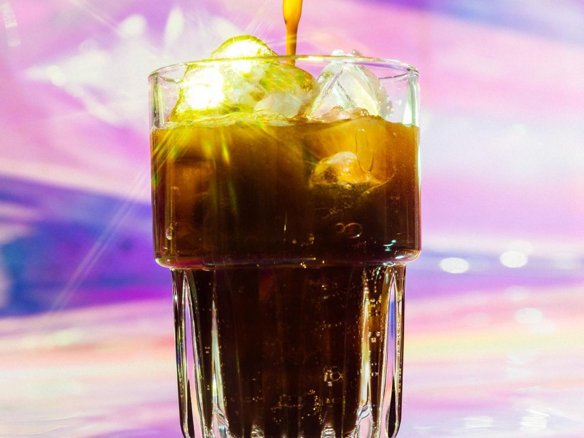 A coffee drink in a clear glass with a pink and purple background
