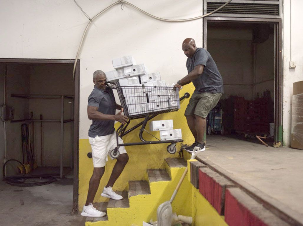 Former NBA player Charles Oakley and Orr Academy basketball coach Lou Adams carry a cart full of Air Jordan sneakers into school for the basketball team. | Max Herman/For the Sun-Times