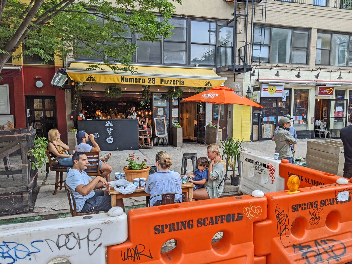 Tables in the street surrounded by orange plastic barriers.