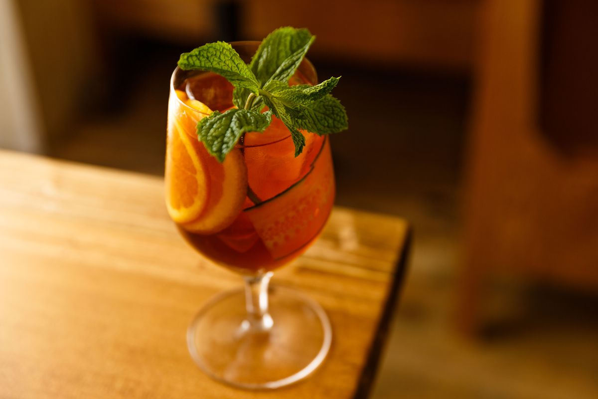 A Pimm's cup with orange and cucumber slices and a mint garnish in a stemmed glass set at the corner of a wooden table