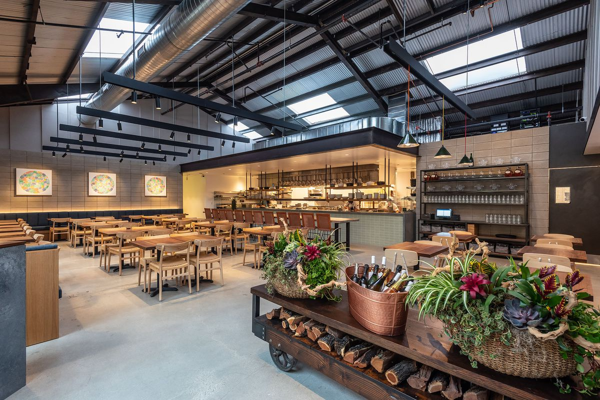 The warehouse-like restaurant space, with tables beyond the entryway, to Birdie G's.