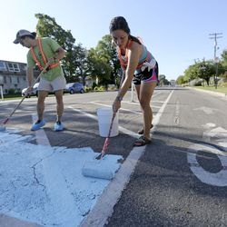 Volunteers Preston DeMaria and Alexis Athens help paint the intersection of 300 East and 700 South in Salt Lake City on Wednesday, Sept. 4, 2019. The Salt Lake City Mayor's Office, Spin and Bike Utah are partnering to turn the intersection into a multi-modal community space.