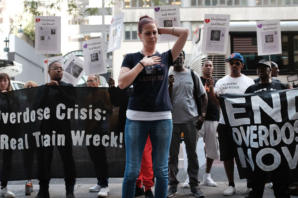 """Activists standing on the street hold banners reading """"The Overdose Crisis: A Real Train Wreck!"""" and """"End overdoses now."""""""