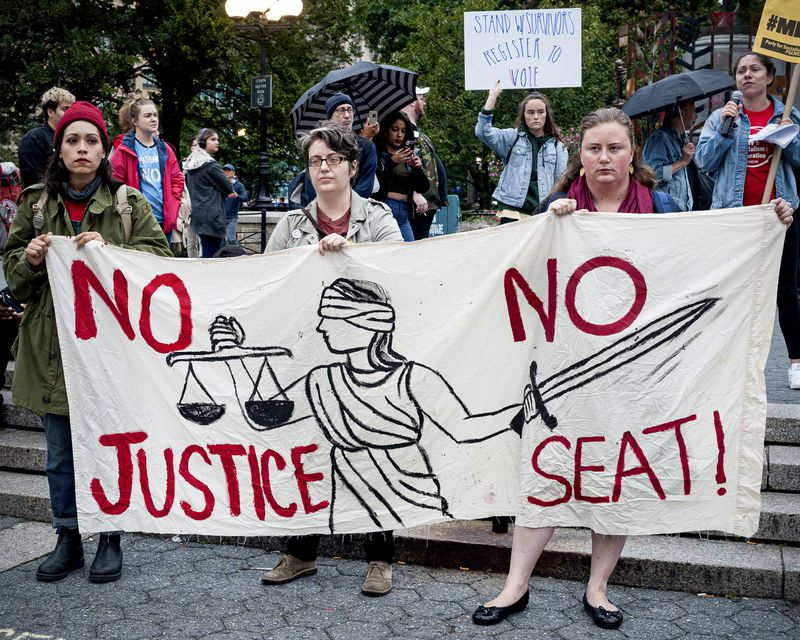 """Three women at a protest against Brett Kavanaugh's nomination to the Supreme Court hold a banner that reads, """"No justice, no seat!"""""""
